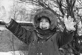 foto of auburn  - Black and white photo of preschool girl with auburn hair and brown eyes is playing with snow outside in a winter day - JPG