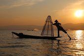stock photo of fishermen  - Traditional fisherman at Inle Lake during the sunset - JPG