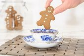 picture of gingerbread man  - Gingerbread man being dunked into a cup of tea with jar of cookies in the background - JPG