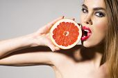 Постер, плакат: Glamour Girl Holding Grapefruit And Tuoching Him With Lips