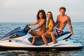 picture of jet-ski  - Multinational friends sitting on a jet ski - JPG