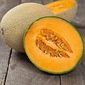 stock photo of muskmelon  - Fresh melons on old wooden background - JPG
