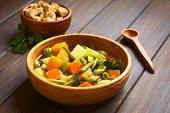 foto of zucchini  - Wooden bowl of vegetable soup made of zucchini green bean carrot broccoli potato and pumpkin with a small bowl of croutons in the back photographed with natural light  - JPG