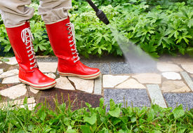 stock photo of pressure-wash  - Person in red gumboots cleaning garden alley with a pressure washer - JPG