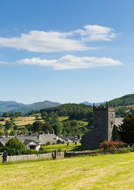 picture of english rose  - Beautiful English country village of Hawkshead Lake District Cumbria UK in summer with blue sky church and pink roses - JPG