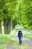 picture of woman boots  - woman wearing rubber boots walking in spring alley - JPG