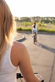 image of pov  - Beautiful young woman riding bike looking at road on bright sunny summer day blurred bicyclist on background focus on model shoulder - JPG