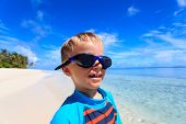 stock photo of goggles  - happy boy in swimming goggles on summer beach - JPG