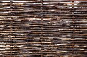 picture of wooden fence  - Old wooden fence interwoven branches background - JPG