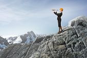 picture of spyglass  - Young woman engineer on rock top looking in spyglass - JPG