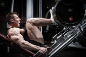picture of training gym  - Man in gym training at leg press to define his upper leg muscles - JPG