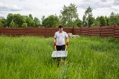 picture of hand-barrow  - man with an empty wheelbarrow in the grass - JPG