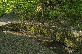 stock photo of ravines  - Stonewall firming creek bed in Golosov ravine in Kolomenskoye park in Moscow - JPG
