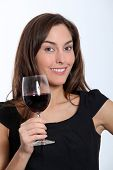 Beautiful woman in black dress tasting red wine