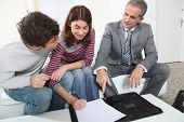 picture of real-estate agent  - Young couple signing renting contract with real estate agent - JPG