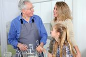 Grandfather, mother and daughter baking