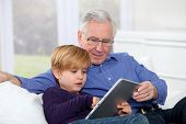 stock photo of grandpa  - Grandpa with little boy using electronic tablet - JPG