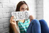 Sad teenage girl sitting near brick wall and holding paper with word HELP poster