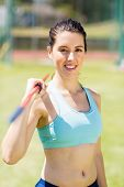 Постер, плакат: Portrait of happy female athlete holding a javelin in stadium