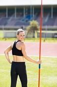 Постер, плакат: Portrait of happy female athlete holding a javelin standing in stadium