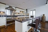 contemporary kitchen with a breakfast bar and polished stone work top