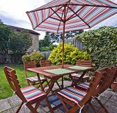 foldable wooden garden furniture with striped umbrella