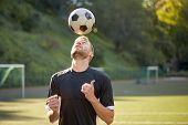 sport, football and people - soccer player playing and juggling ball using header technique on field poster