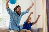 Excited father and son watching television in living room poster