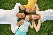 stock photo of summer fun  - Lying family with children on green grass - JPG