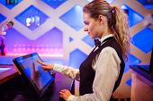 Side view of young barmaid using modern cash register at bar counter poster