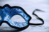 closeup of an elegant blue and black carnival mask on a rustic wooden surface poster