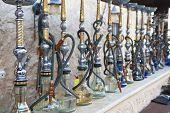 Arabic shisha, sometimes called hookah, waterpipes lined up on a bar for customers in a restaurant in an Arabic country.