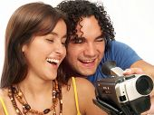 Young couple sharing and watching a camcorder. Young couple watching a video camera screen.