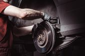 A Mechanic In The Service Center Checks The Suspension Of The Car. Performs Seasonal Wheel Replaceme poster