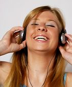 Young woman listening music using headphones.