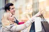Happy couple at shop window doing Christmas shopping poster