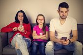 Parents Busy With Mobile Phones And Angry Little Girl/parents Busy With Mobile Phones And Their Angr poster