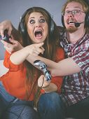 Couple Enjoying Leisure Time By Playing Video Games Together, Man And Woman Being Emotional By Game. poster