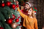 Man Husband In Warm Santa Hat With Woman Wife In Elf Hat At Home Decorating Christmas Tree With Ligh poster