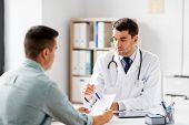 medicine, healthcare and people concept - doctor showing prescription to patient at medical office i poster