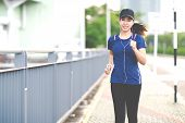 Young Attractive Asian Runner Woman Running In Urban City Street Or Foot Path Way Listen To Music We poster