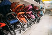 Row of baby strollers on shelf in store, nobody poster