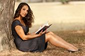 outdoor shot of young reading book leant against tree