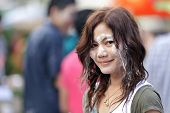 beautiful asian woman, face covered with wet powder during songkran new year festival in thailand