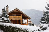Christmas Wooden Mansion In Mountains On Snowfall Winter Day. Cozy Chalet On Ski Resort Near Pine Fo poster