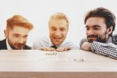 Three Men Looking At Clerical Buttons On Table. April Fools Day. Businessman In Office. April Jokes. poster