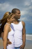 picture of married couple  - Interracial couple standing on a beach both wearing white tank tops - JPG