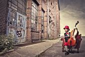 stock photo of cello  - Young man sitting on an armchair on a city street and playing the cello - JPG