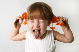 stock photo of sticking out tongue  - Head and hands shot of Little girl sticking out her tongue at the camera for fun - JPG