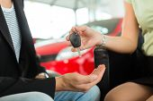 Man at a car dealership buying an auto, the female sales rep giving him the key, macro shot with focus on hands and key